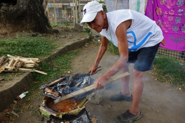 "This old man was cooking ""bibingka"" with fire on top and below"