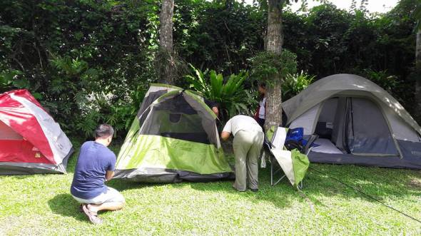 pitching tents, setting up mattresses and white linen beddings